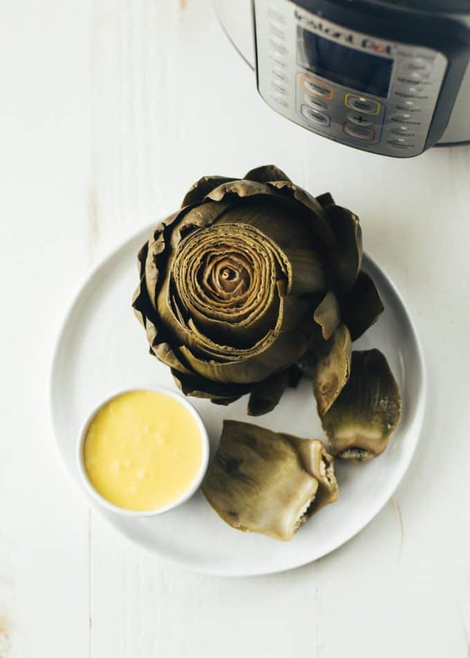 Instant Pot Steamed Artichoke on a white plate, next to a small white bowl of hollandaise sauce