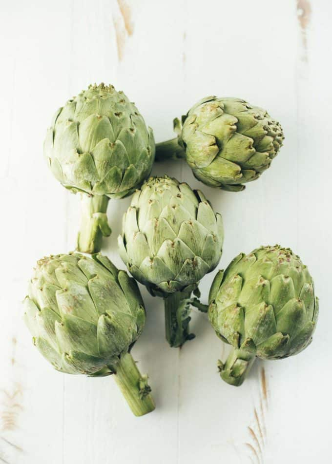 5 whole artichokes lying on a white table