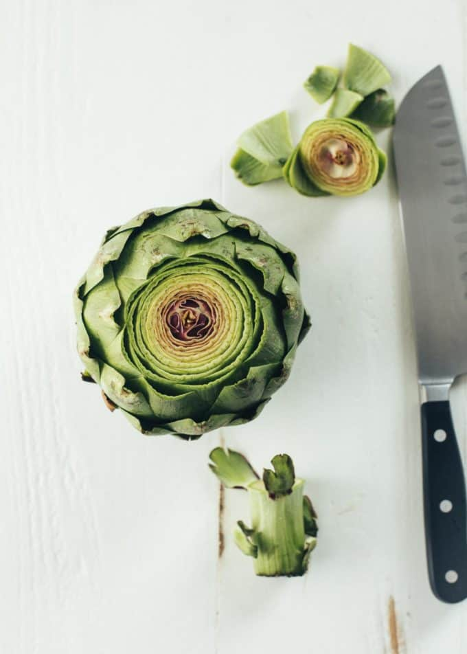 an artichoke with the top sliced off next to a knife on a white table