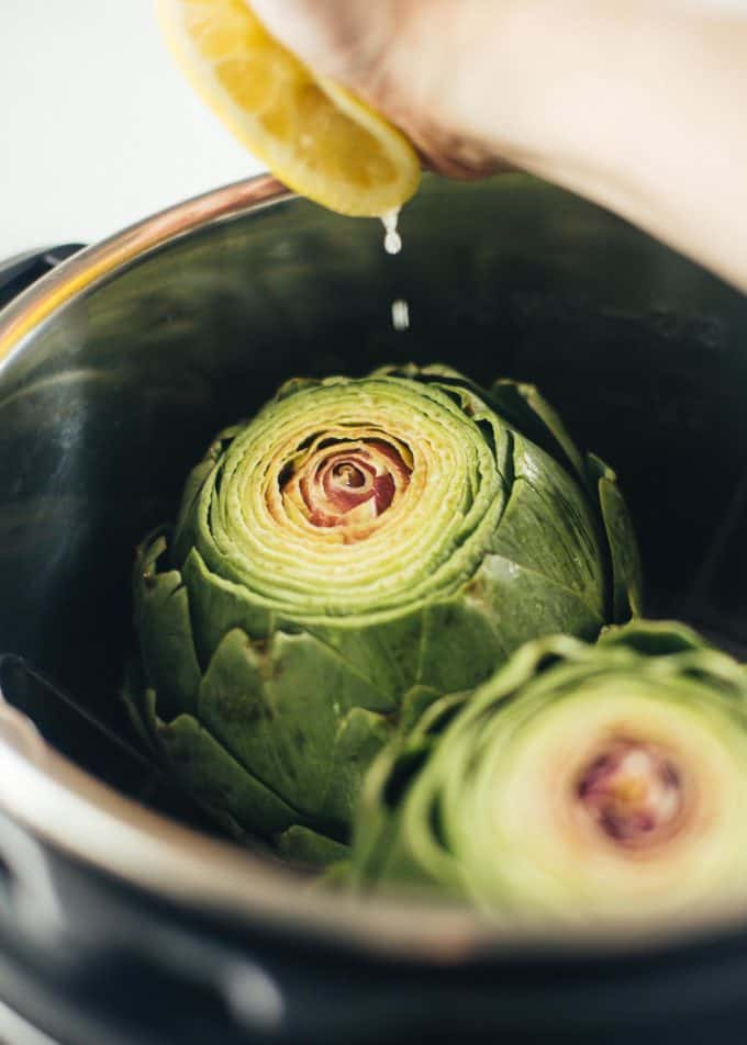 squeezing a lemon over artichokes in an instant pot