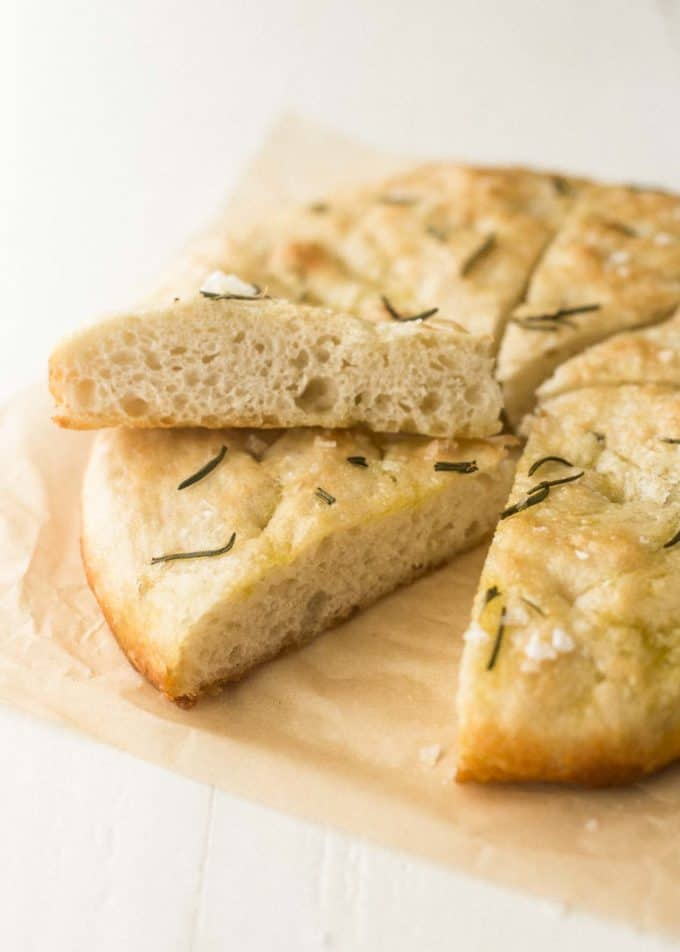 No Knead Focaccia cut into slices on a piece of parchment paper