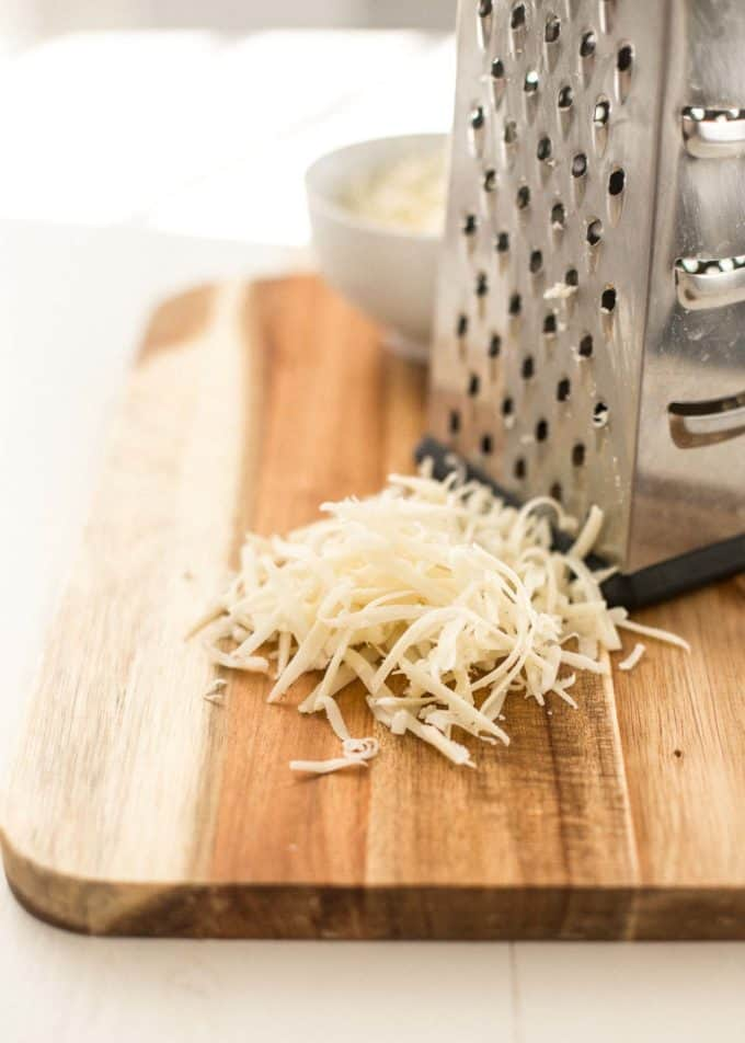 grated gruyere cheese on a cutting board next to a cheese grater