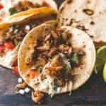 chicken carnitas tacos on a grey table