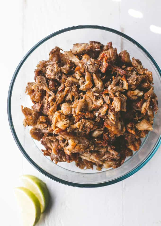 Slow cooker chicken carnitas in a clear glass bowl