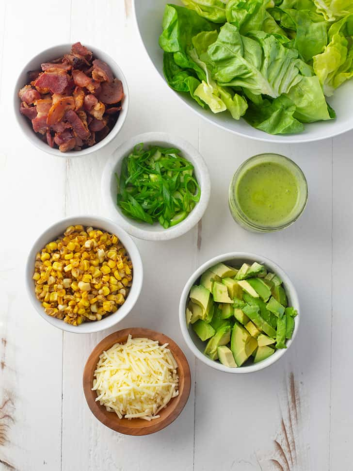 bacon, corn, avocado, lettuce, green onions, parmesan cheese and salad dressing in small bowls on a white table