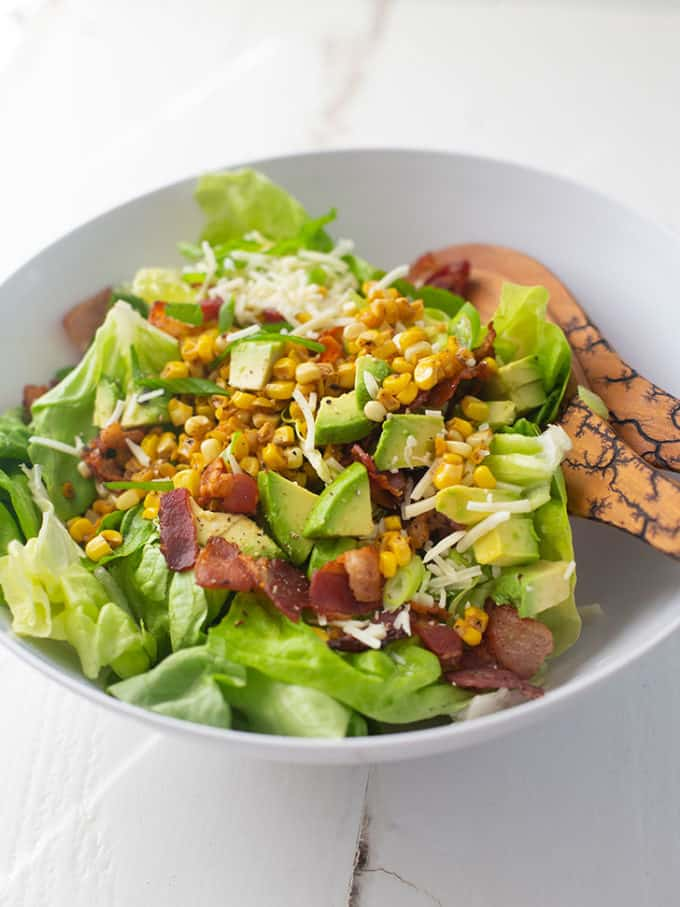 bacon, corn and avocado salad in a white bowl with wooden spoons