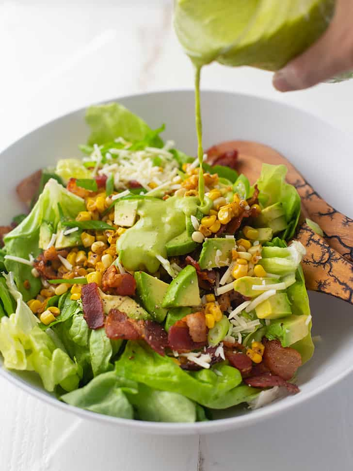 pouring dressing on bacon, corn and avocado salad