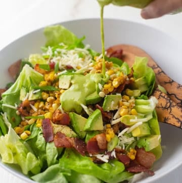 bacon, corn and avocado salad in a white bowl