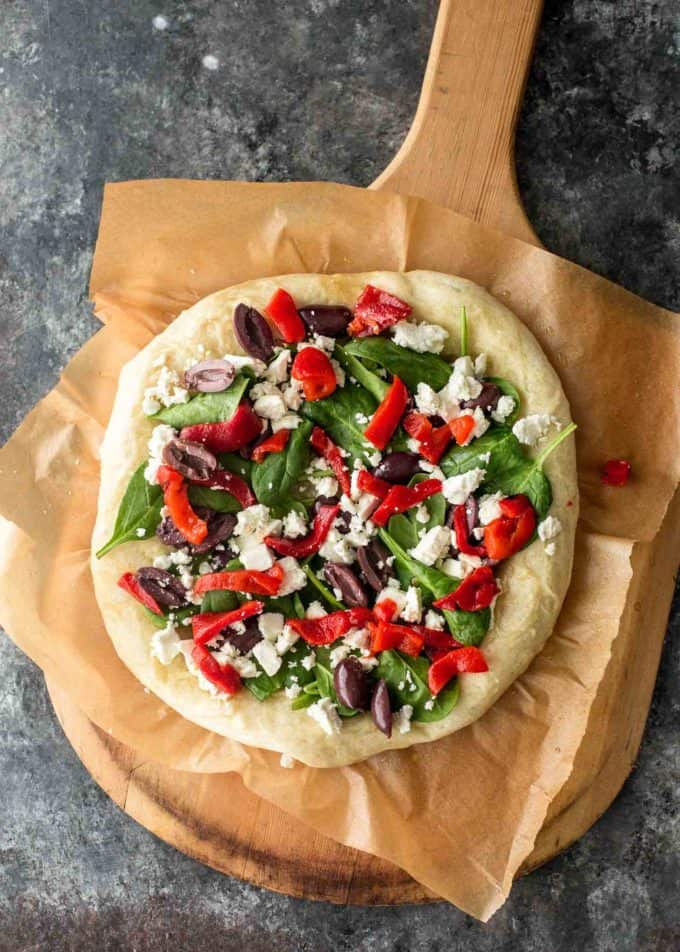 unbaked Greek Pizza on parchment paper