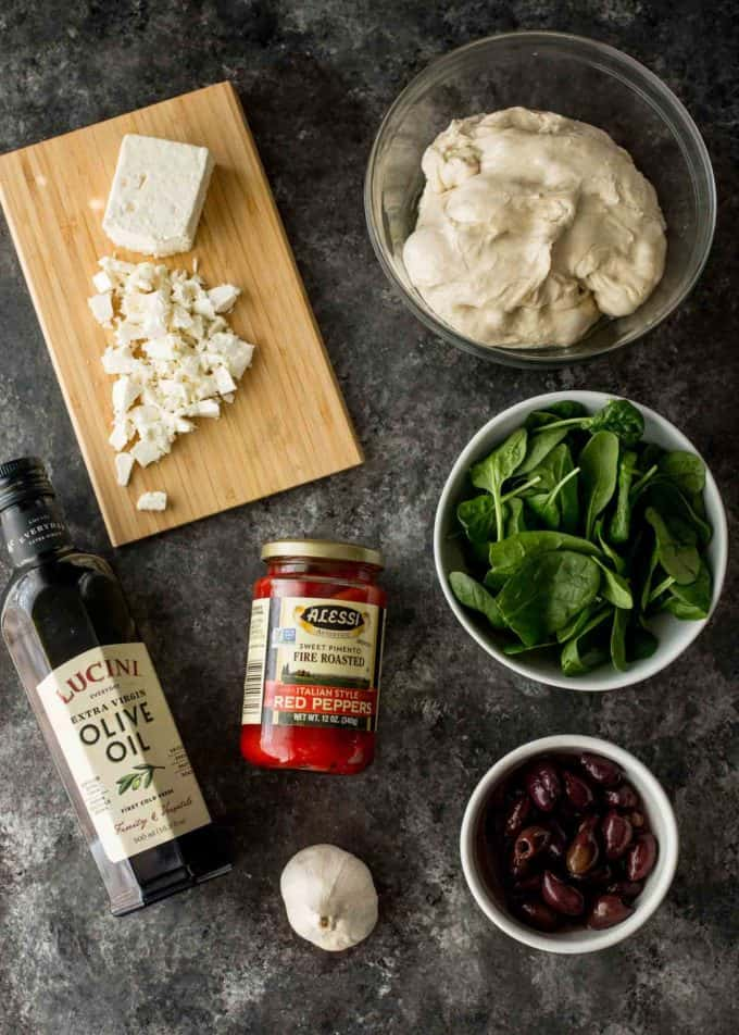 Greek Pizza ingredients: pizza dough, red peppers, olive oil, garlic, baby spinach, olives and feta