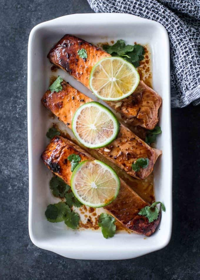 lime topped broiled salmon in a white baking dish