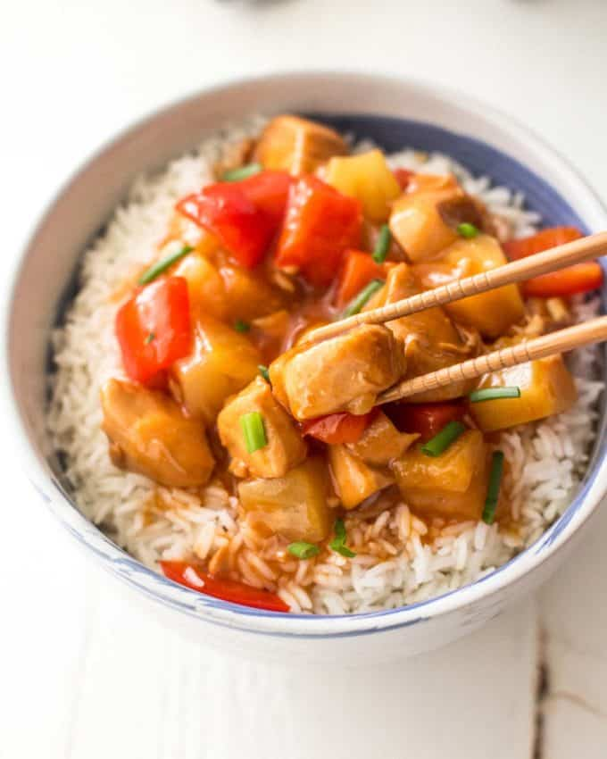 instant pot sweet and sour chicken over rice in a white bowl with chopsticks