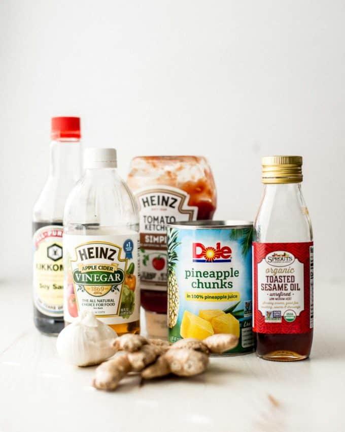 soy sauce, vinegar, pineapple chunks, ketchup, sesame oil, garlic, and ginger on a white table