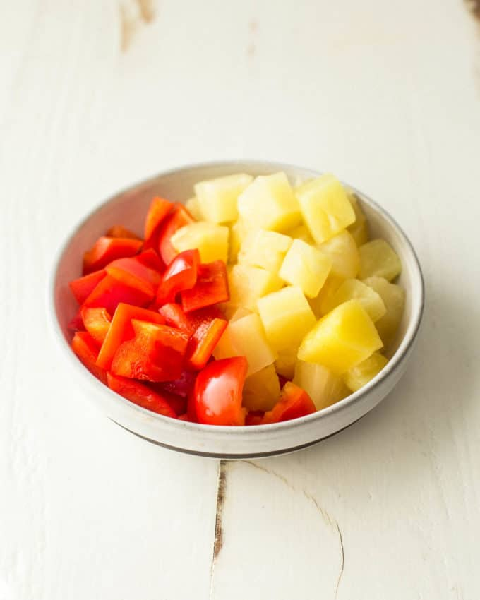 pineapple chunks and red bell pepper pieces in a small white bowl