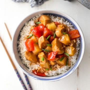 instant pot sweet and sour chicken over rice in a bowl next to chopsticks