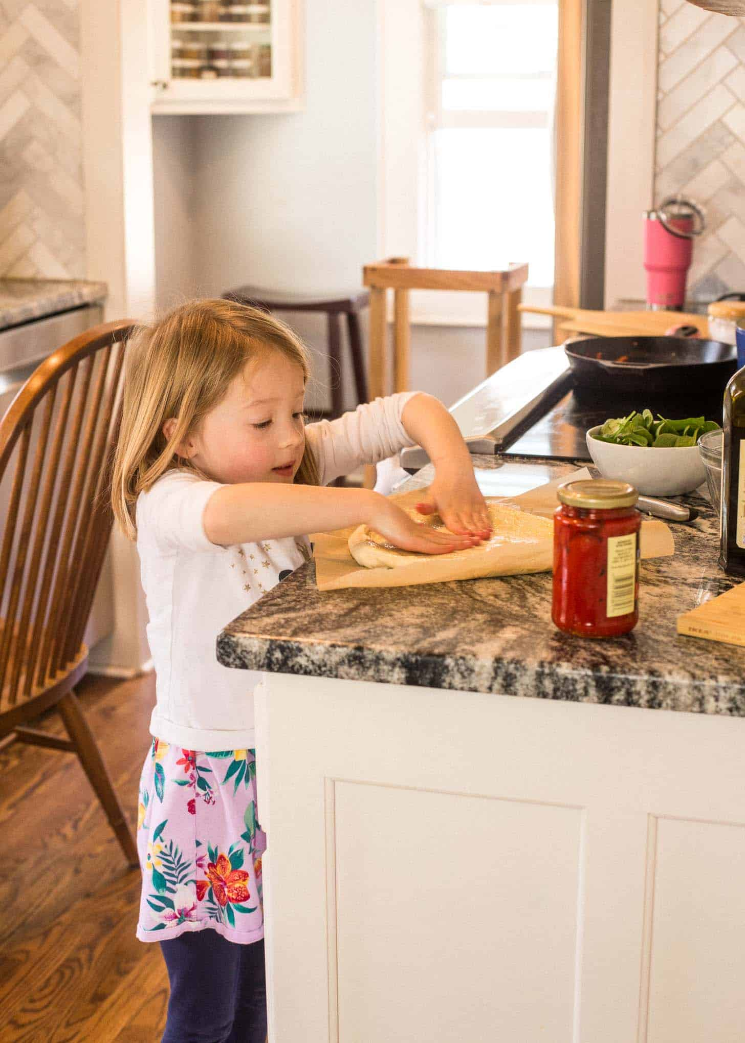 Molly helps to roll out pizza dough
