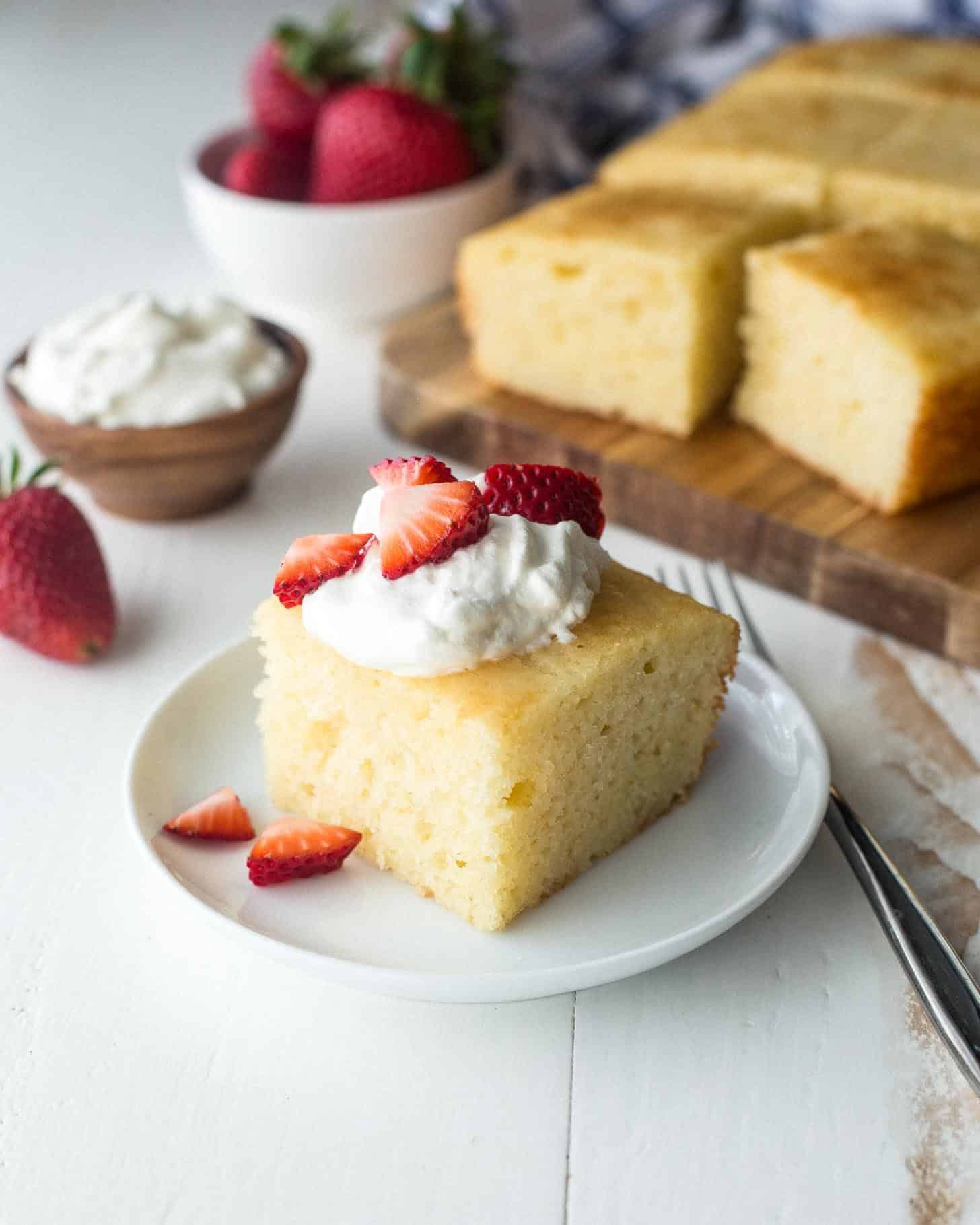semolina yogurt cake topped with whipped cream and berries