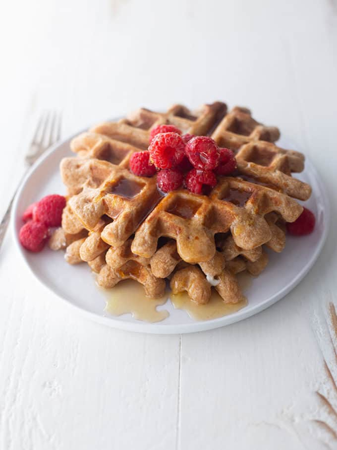 Overnight whole wheat waffles on a white plate, topped with raspberries and syrup