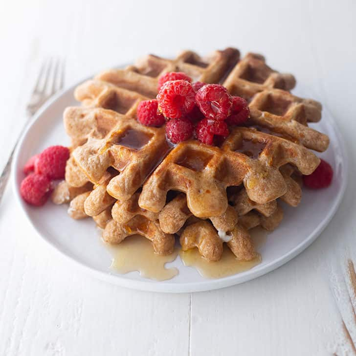 overnight yeasted whole wheat waffles on a white plate with raspberries