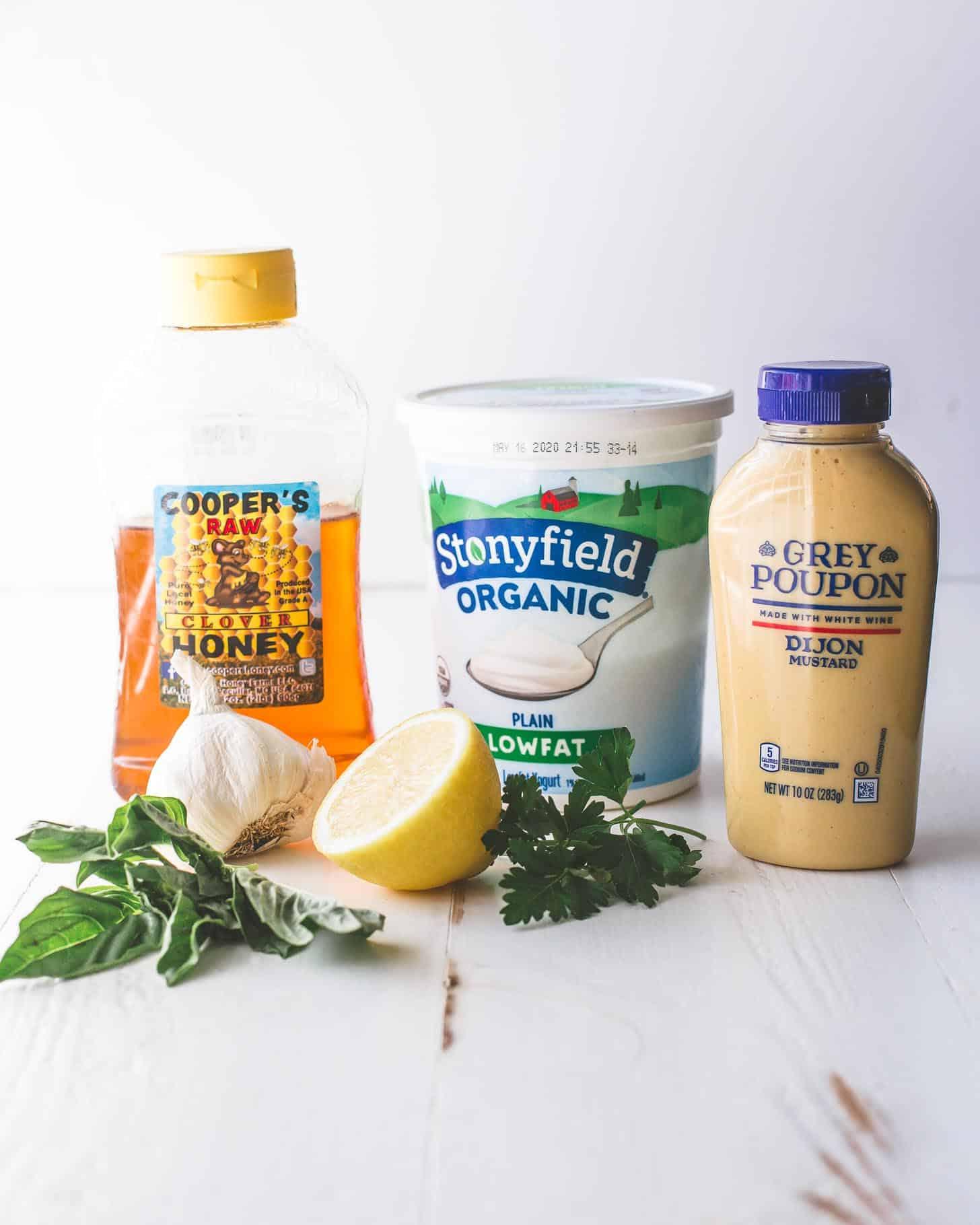 ingredients for yogurt herb dressing -- honey, yogurt, dijon mustard, garlic, lemon, cilantro, and basil