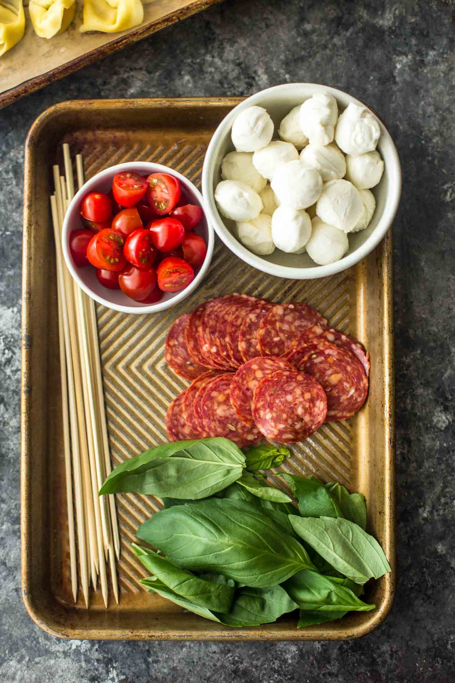 ingredients for pasta salad skewers, including mozzarella pearls, basil, cherry tomatoes and pepperoni