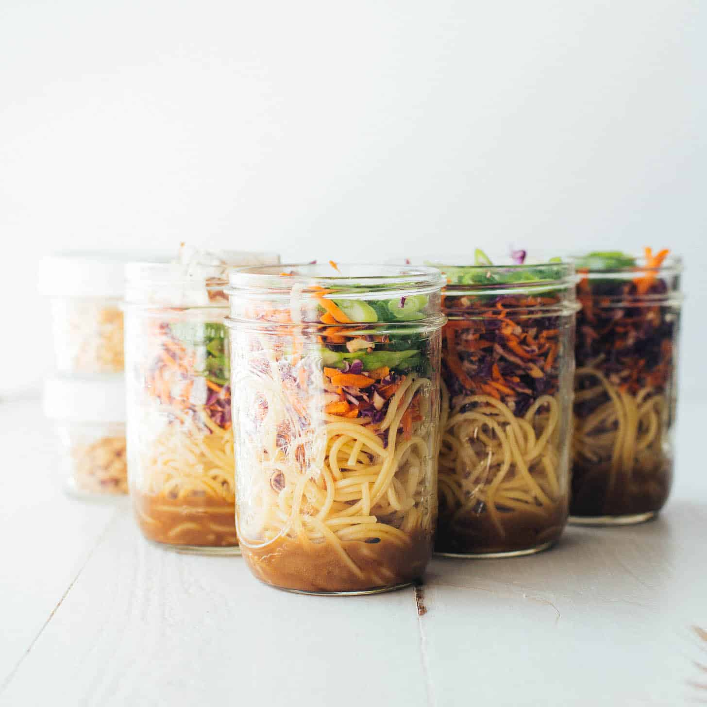 6 jars of sesame noodle salad on a white table