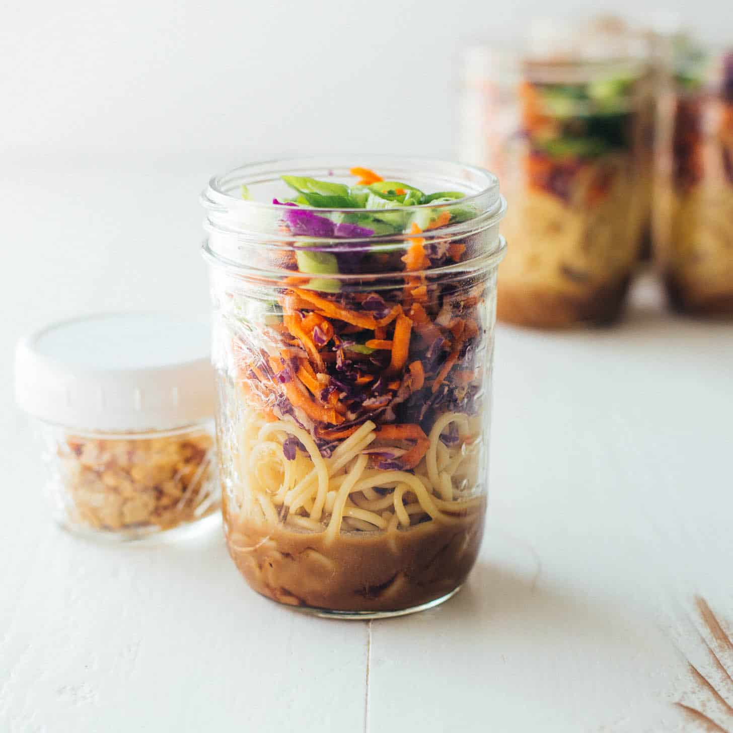 Sesame noodle salad in a mason jar on a white table