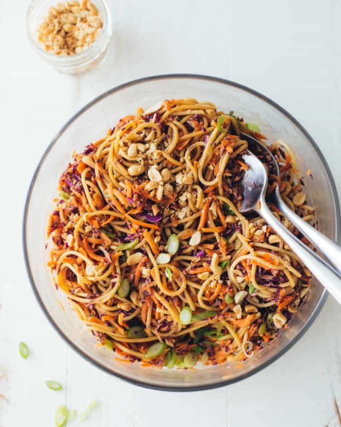 Sesame Noodle Salad in a clear bowl with 2 large spoons