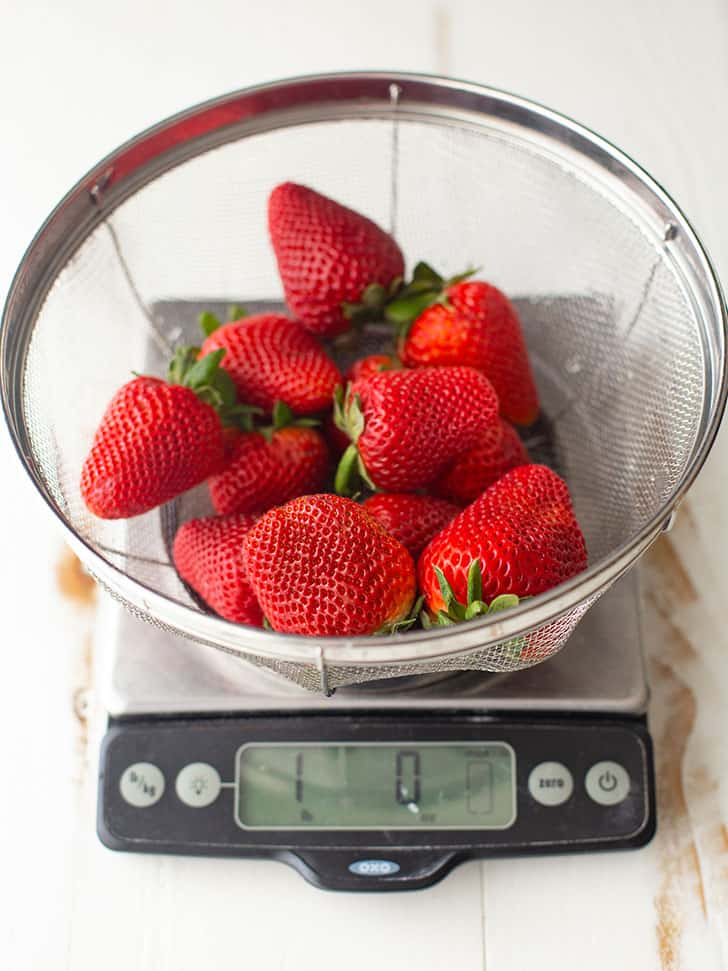 fresh strawberries in a strainer on a kitchen scale
