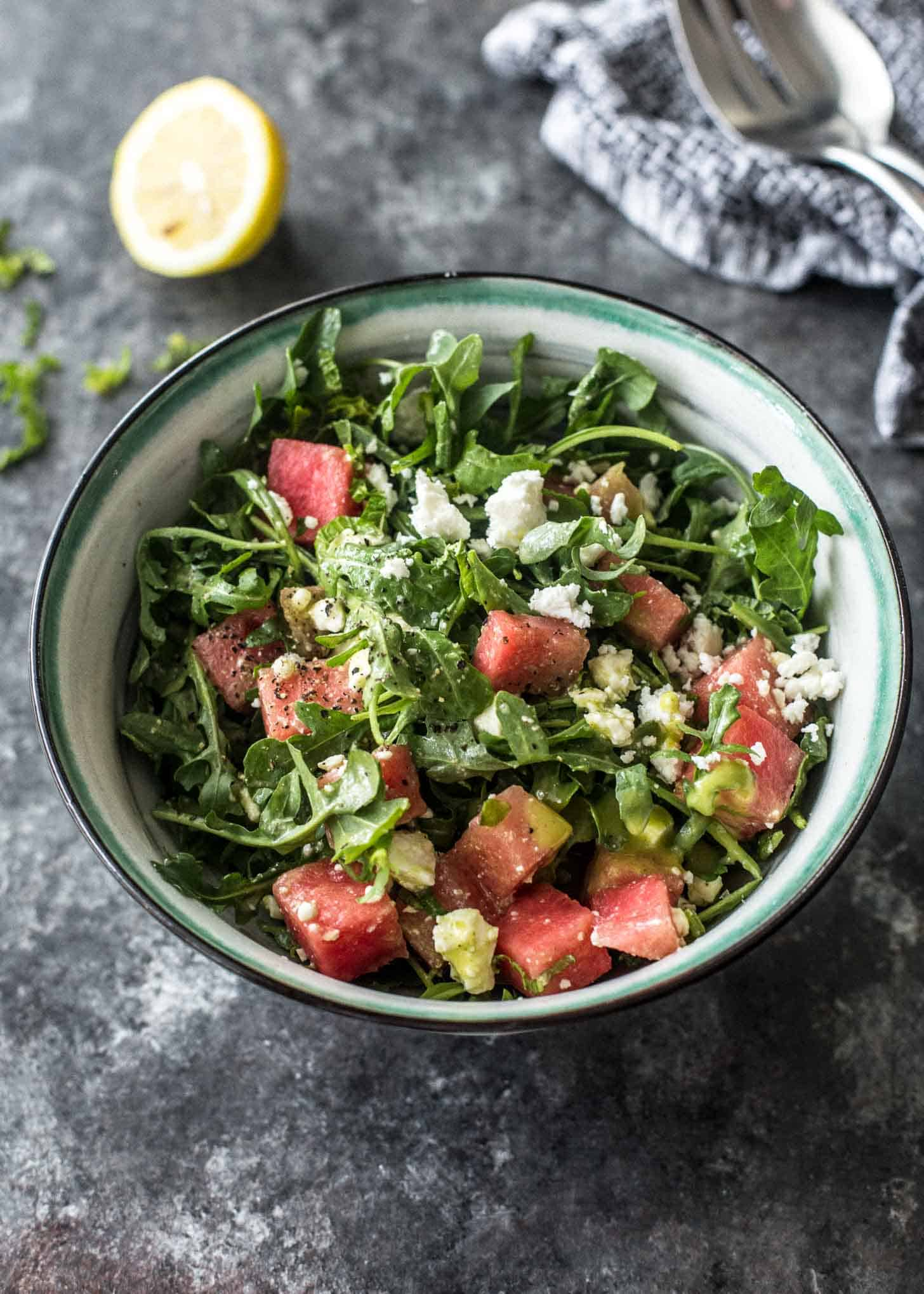 watermelon, feta and arugula salad in a white bowl on a grey table