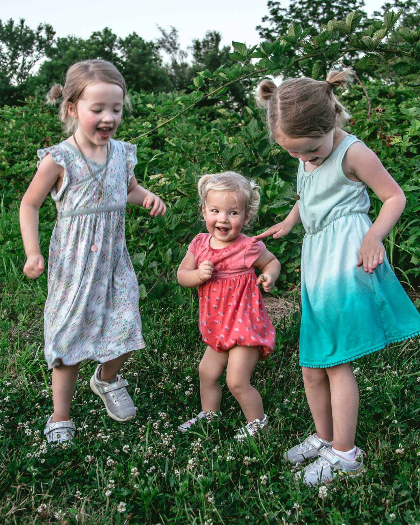 3 young girls dancing in the blackberry field