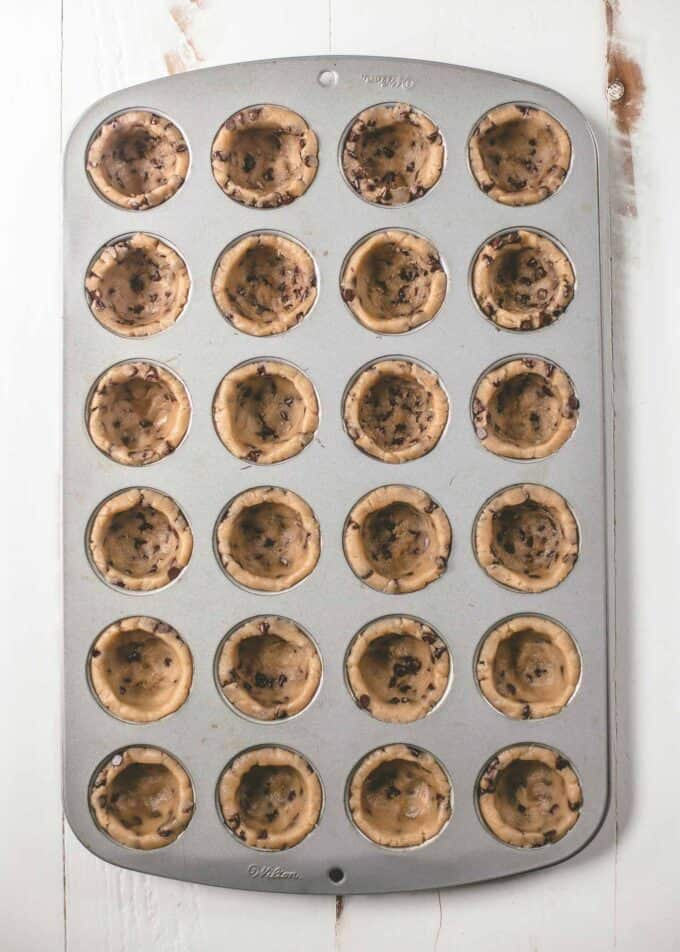 chocolate chip cookie dough in a muffin tin