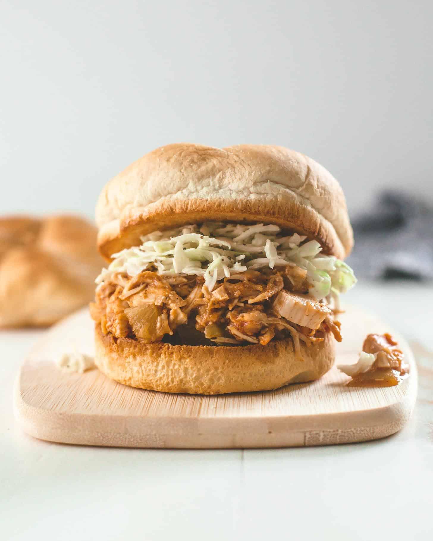 slow cooker hawaiian chicken on a bun with slaw