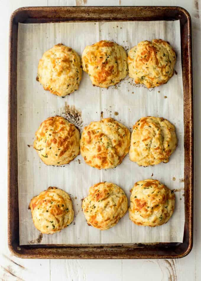 cheddar drop biscuits on a parchment lined sheet pan