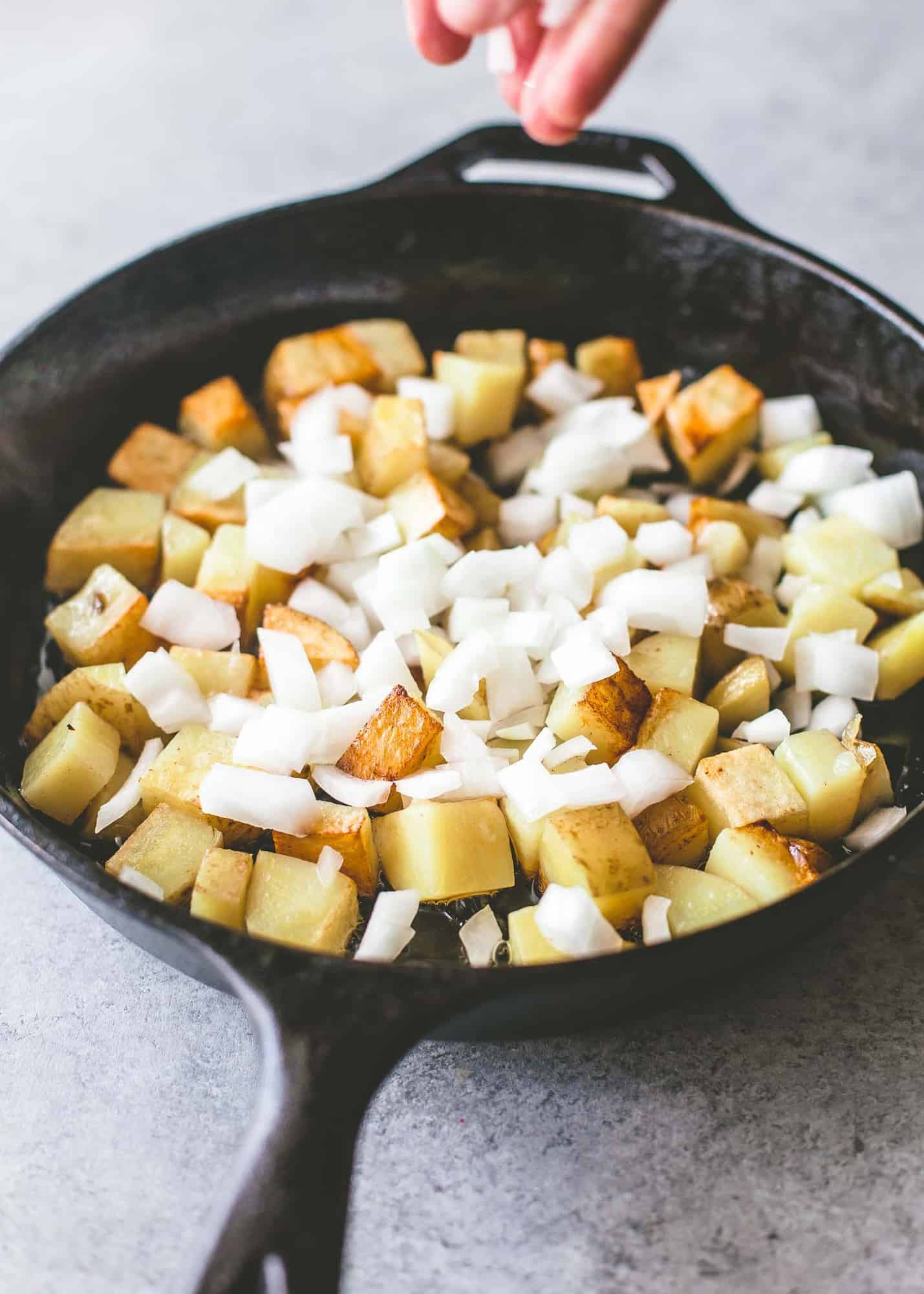 adding potatoes and onions to a cast iron skillet
