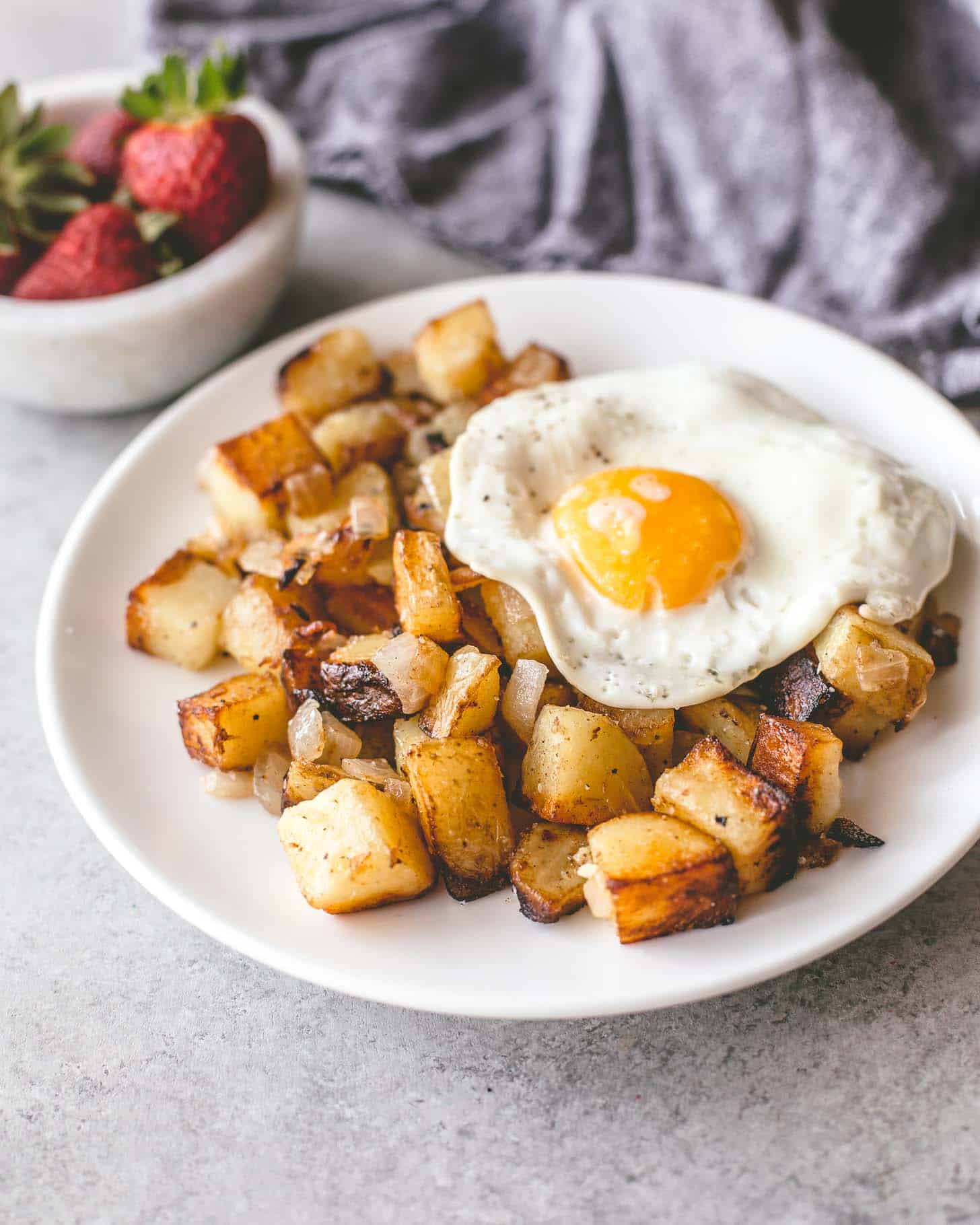 skillet home fries on a white plate topped with a fried egg
