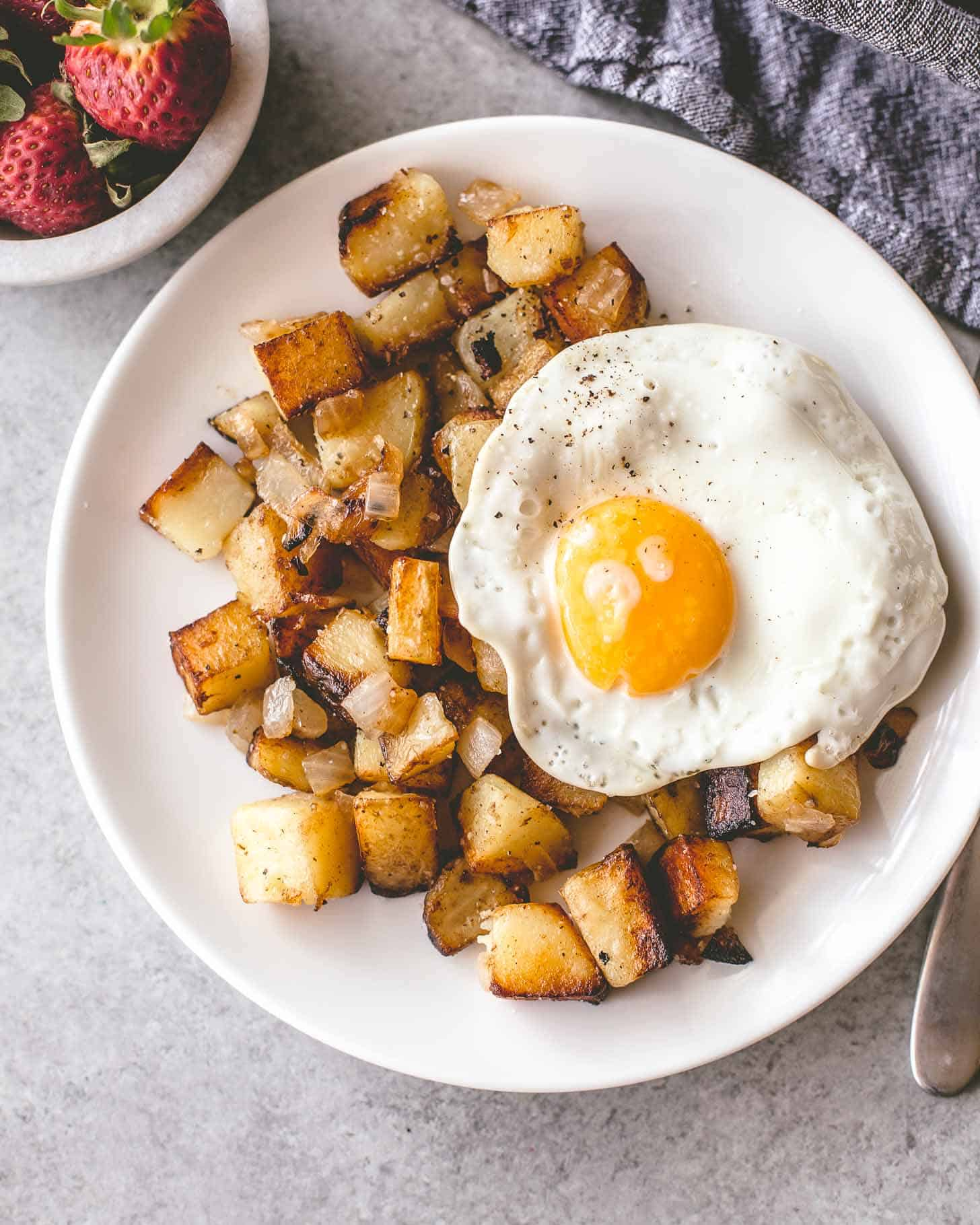 home fries on a white plate topped with a fried egg