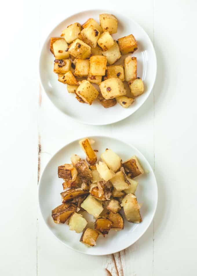 2 white plates of home fries on a white table