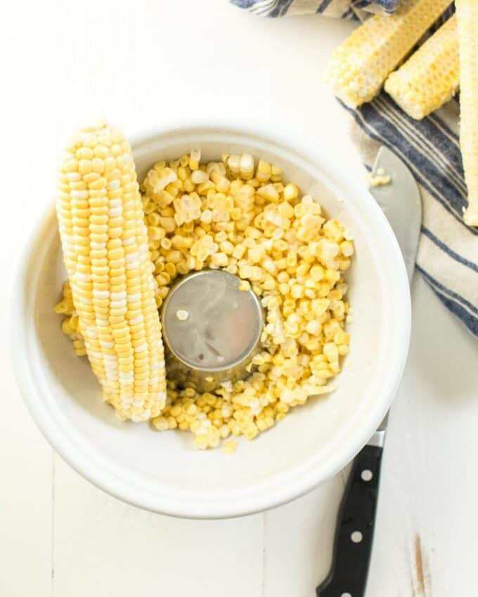 cutting corn off the cob in a white bowl