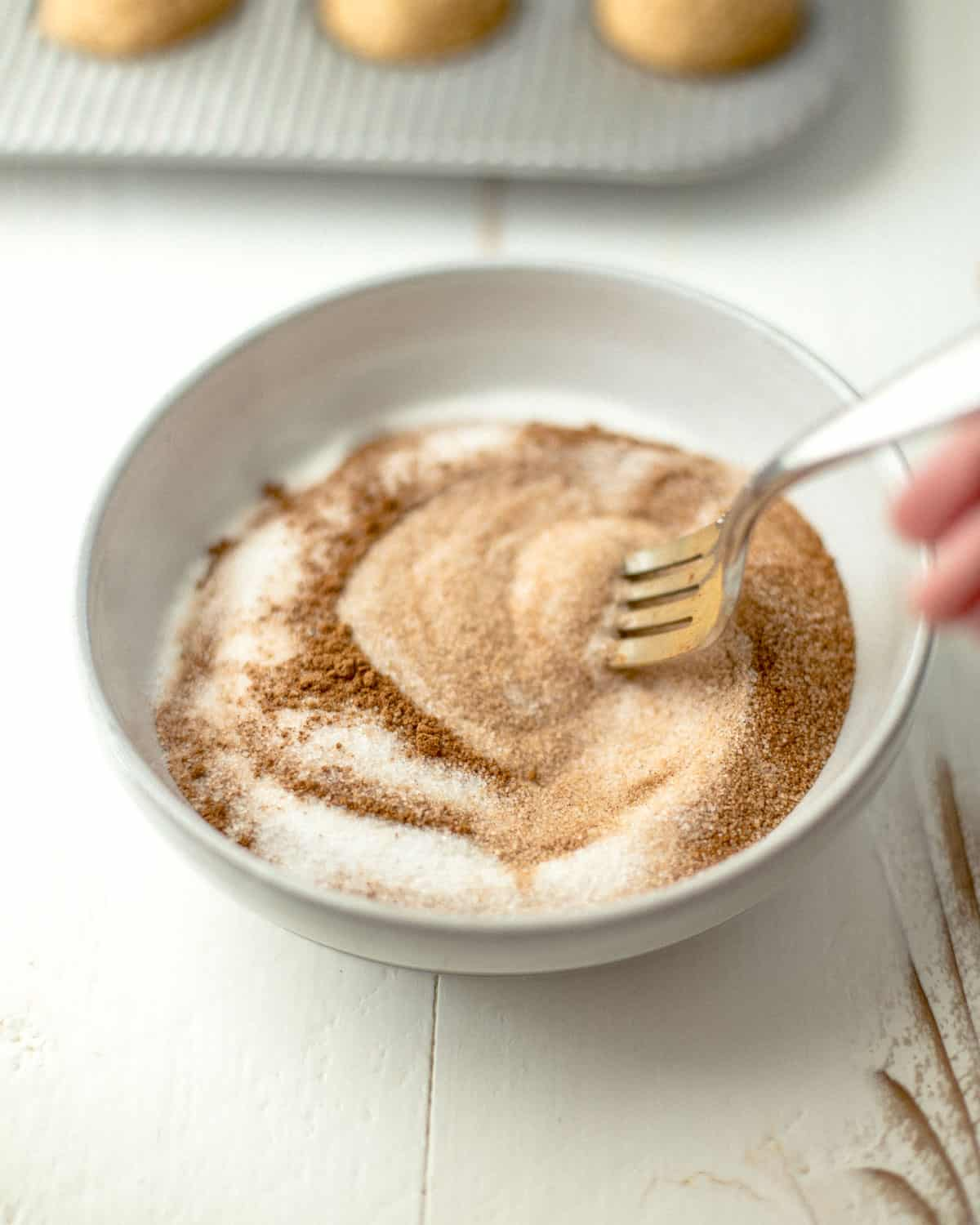 mixing cinnamon and sugar in a white bowl