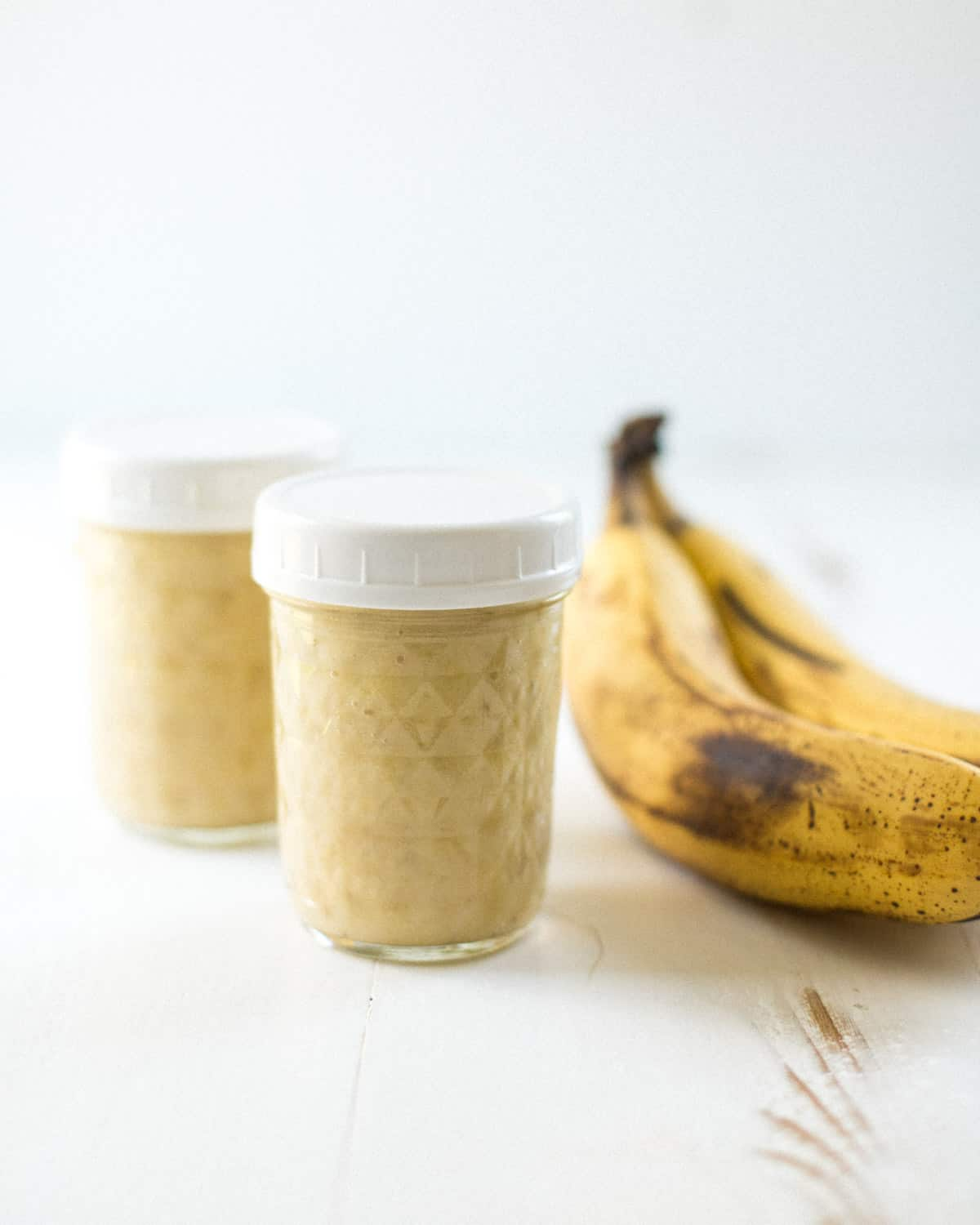 a banana and 2 glass jars on a white table