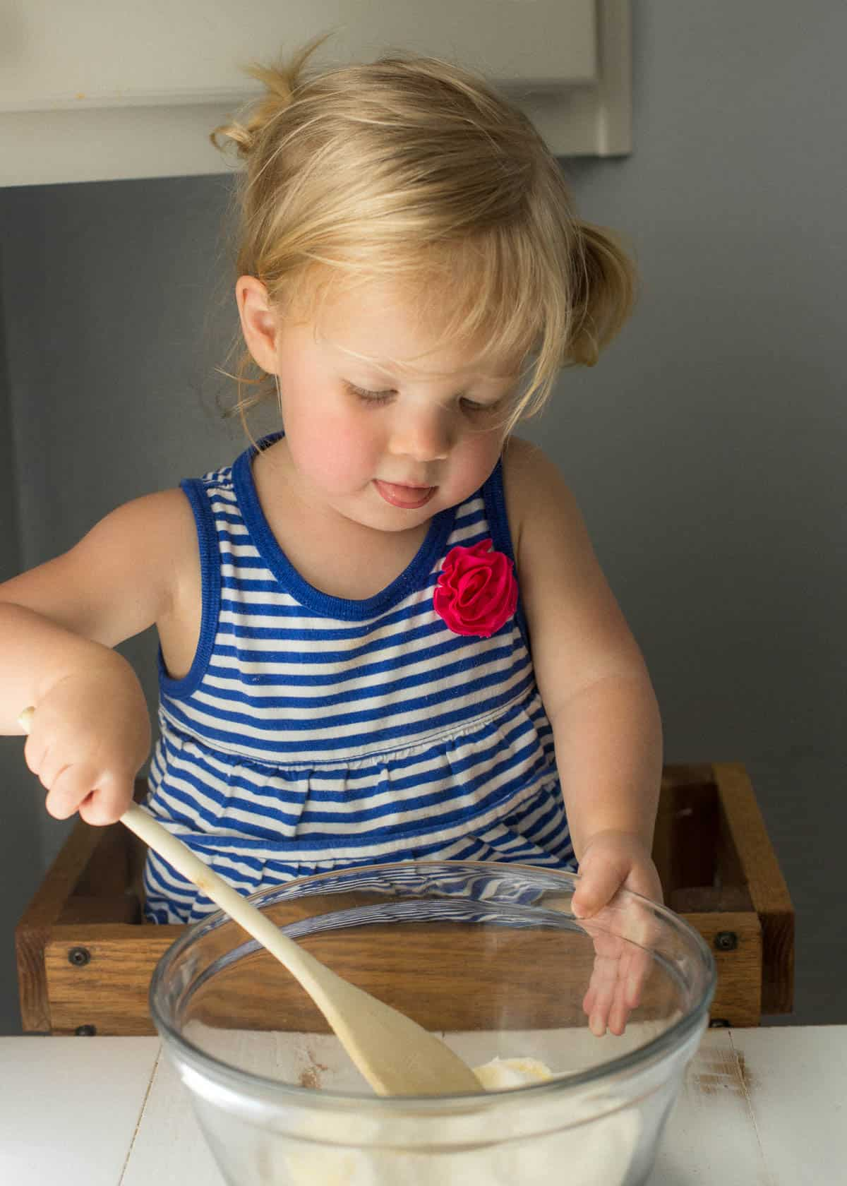 little girl stirring ingredients in a mixing bowl