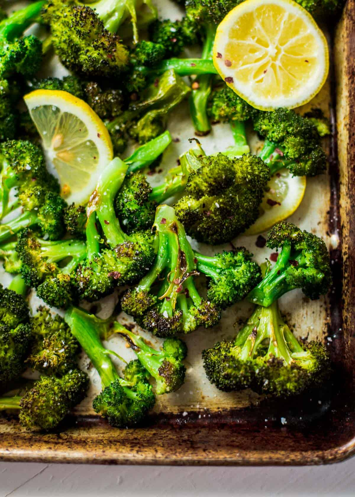 roasted broccoli and lemon slices on a sheet pan