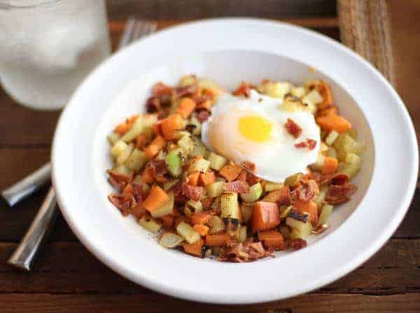 Sweet Potato, Apple and Bacon Hash in a white bowl topped with a fried egg