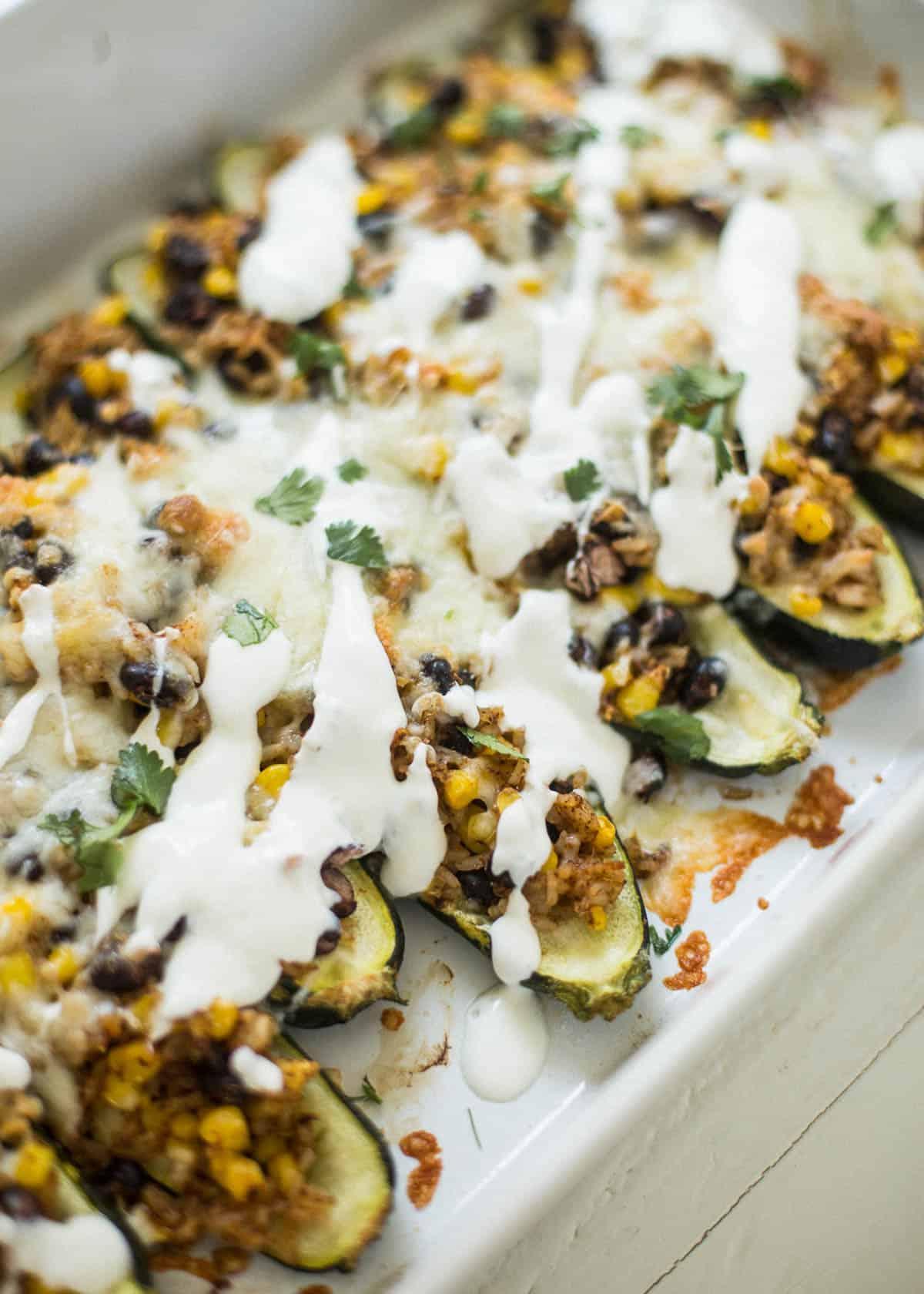 stuffed zucchini boats on a white tray
