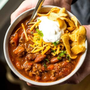 chili with chips and sour cream in a bowl held by hands