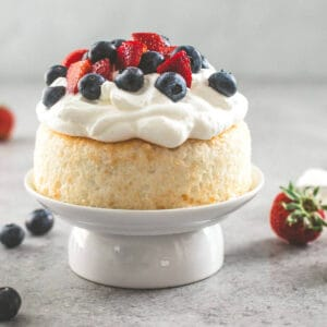 cake with cream and fruit on top on a white cake plate