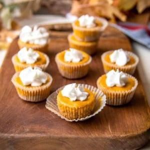 pumpkin cheesecake bites on a wooden board