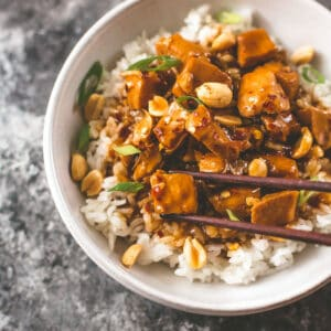kung pan chicken in a bowl with rice and chopsticks