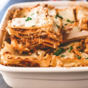 a slice of lasagna in a baking dish